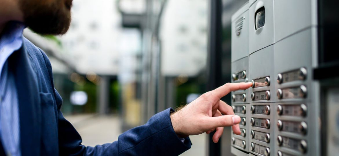 Man pushing the button and talking on the intercom